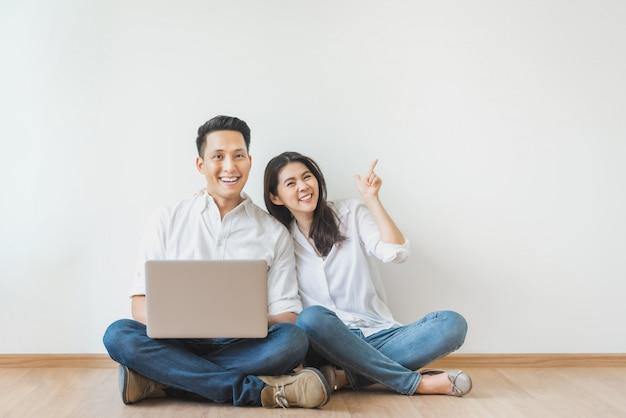 Pareja asiática sentada en el piso usando una computadora portátil en la sala blanca Foto Premium