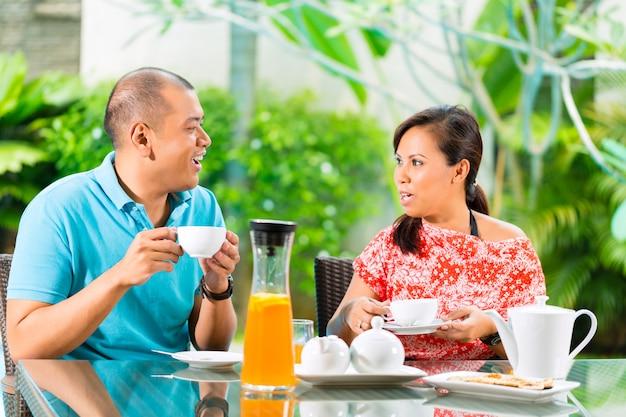 Pareja asiática tomando un café en el porche de casa Foto Premium