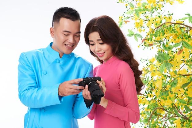 Pareja asiática en traje tradicional brillante revisando fotos en la cámara junto a la flor de mimosa Foto gratis