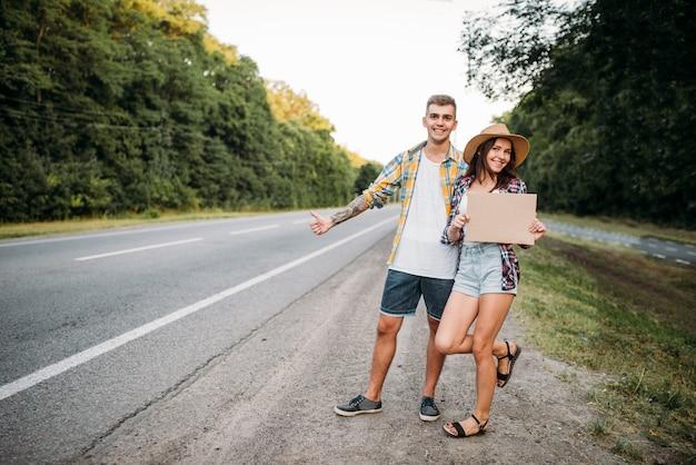 Pareja de autostop tiene cartón en blanco con espacio de copia. aventura de autostop de hombre y mujer jóvenes. autostopistas felices en la carretera Foto Premium