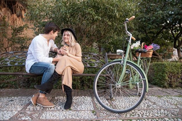 Pareja en el banco con bicicleta y flores. Foto gratis