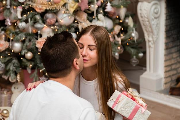 Pareja besándose con regalo delante del árbol de navidad Foto gratis