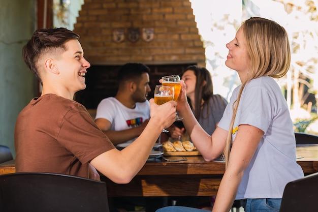 Pareja brindando cerveza en el bar restaurante al aire libre. concepto de estilo de vida con gente feliz divirtiéndose juntos. concéntrese en la pareja de delante. Foto Premium