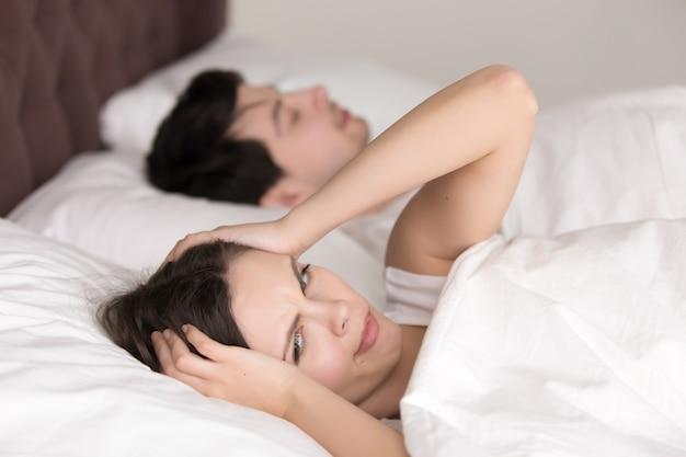 Pareja en la cama, mujer que sufre de insomnio, dolor de cabeza, ronquidos Foto gratis