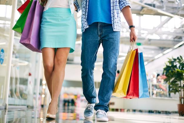 Pareja caminando por el centro comercial con bolsas de la compra   Foto  Gratis