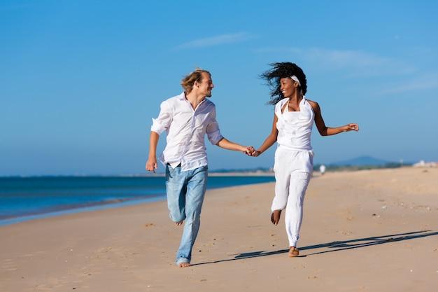 Pareja caminando y corriendo en la playa Foto Premium