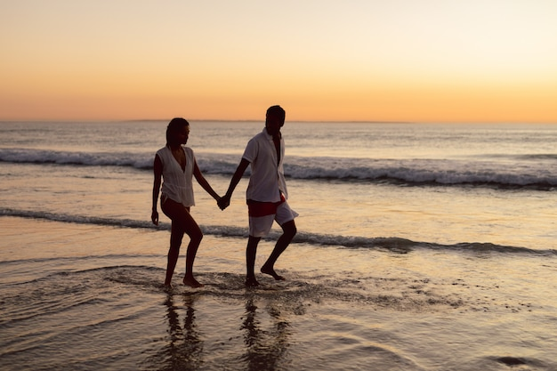 Pareja caminando de la mano en la playa Foto gratis