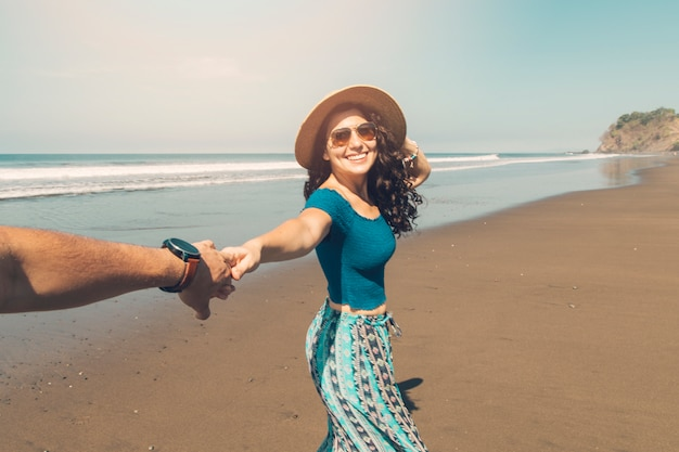 Pareja caminando por la orilla del mar Foto gratis
