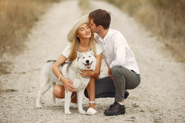 Pareja en un campo de otoño jugando con un perro Foto gratis