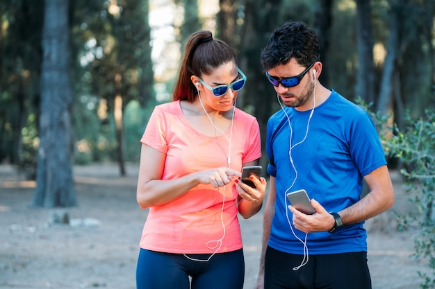 Pareja caucásica viendo la aplicación móvil y haciendo ejercicio en un parque Foto Premium