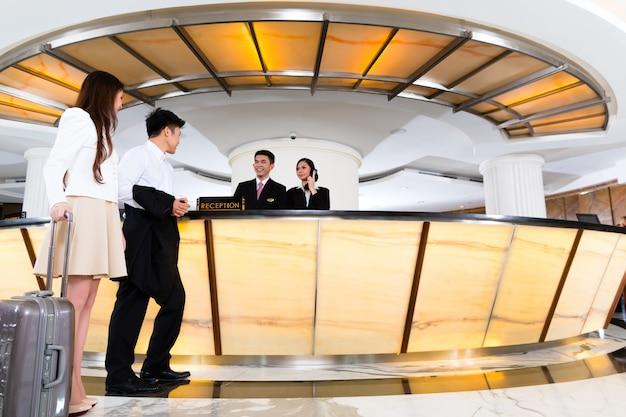 Pareja china asiática llegando a la recepción del hotel Foto Premium