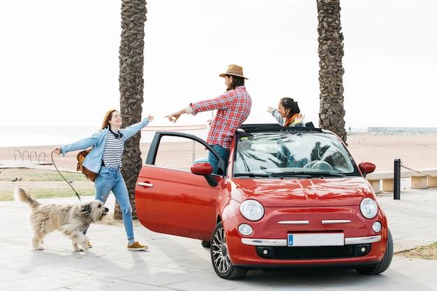 Pareja en coche saludo mujer con perro al aire libre Foto gratis