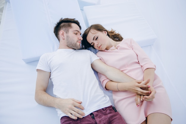 Pareja cogida de la mano tumbada en una cama doble y ella duerme Foto gratis