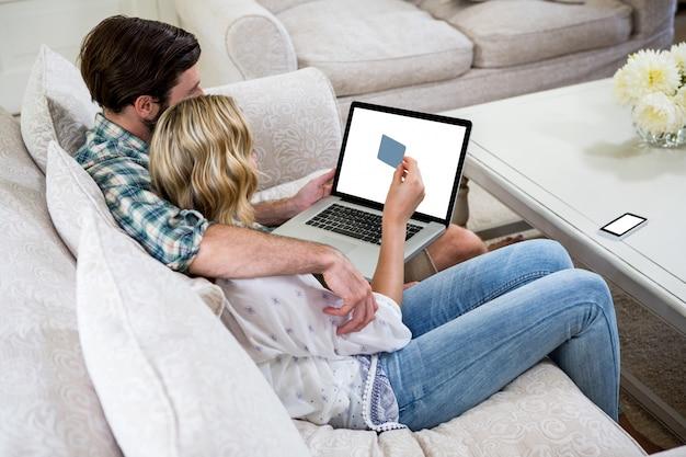 Pareja de compras en línea mientras está sentado en el sofá Foto Premium