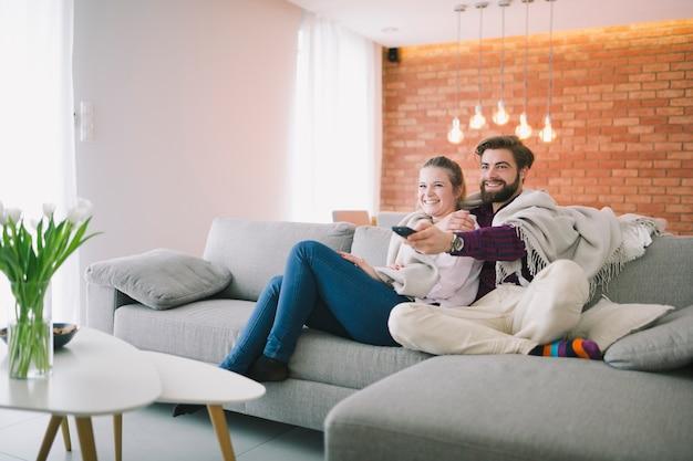 Pareja en cuadros viendo televisión Foto gratis