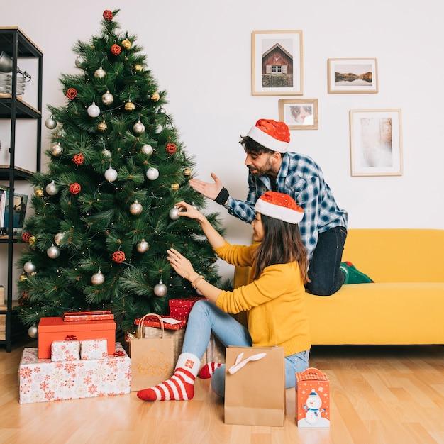 Pareja decorando árbol de navidad en casa | Descargar Fotos gratis