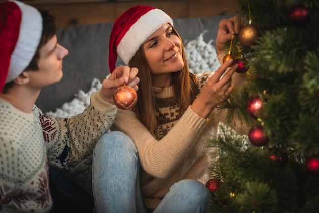 Pareja decorando el árbol de navidad Foto gratis