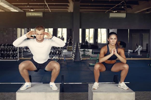 Pareja deportiva en un entrenamiento de ropa deportiva en un gimnasio Foto gratis
