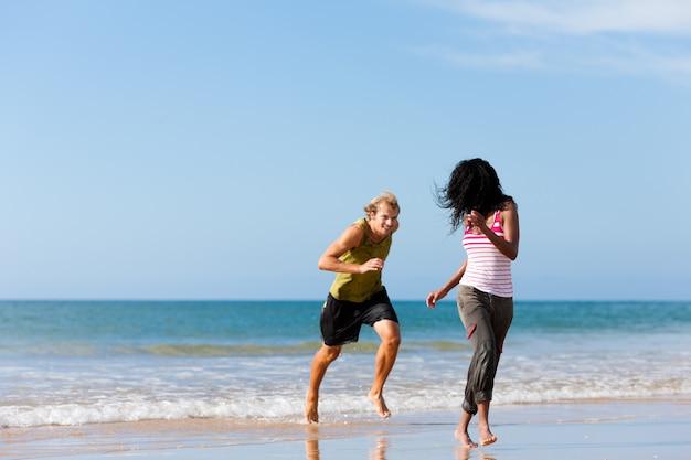 Pareja deportiva jugando en la playa Foto Premium