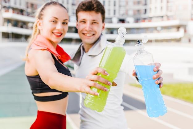 Pareja deportiva mostrando bebidas energéticas Foto gratis