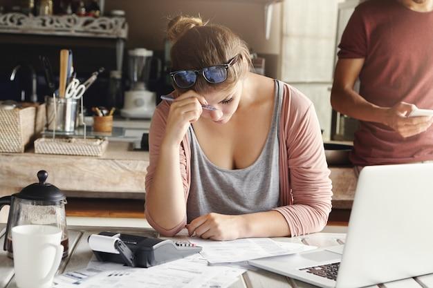 Pareja deprimida frente a problemas de crédito. esposa estresada luciendo exhausta mientras hace cuentas en casa, se esfuerza por recortar los gastos familiares, sostiene la pluma y hace los cálculos necesarios en la calculadora Foto gratis