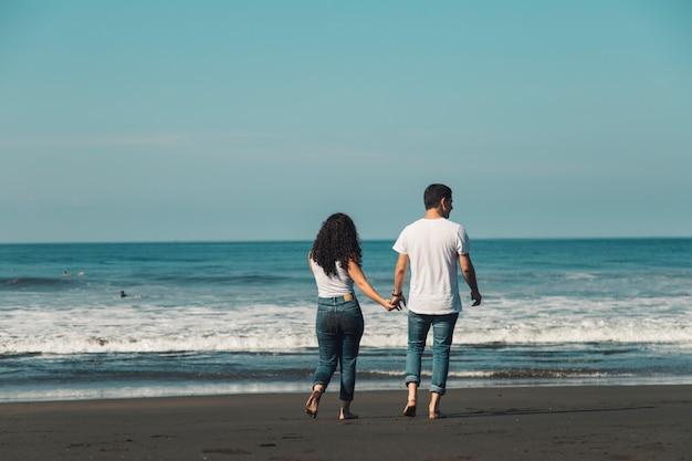 Pareja va descalza en la arena al mar Foto gratis