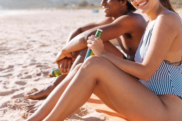 Pareja descansando en la playa con bebidas Foto gratis