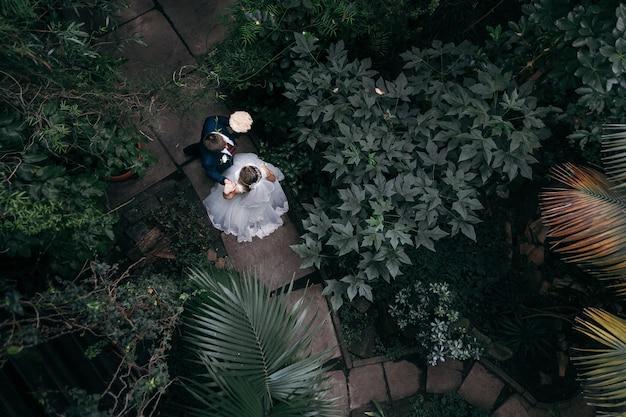 Pareja en el día de la boda en el parque. vista superior. matrimonio. irreconocible. Foto Premium