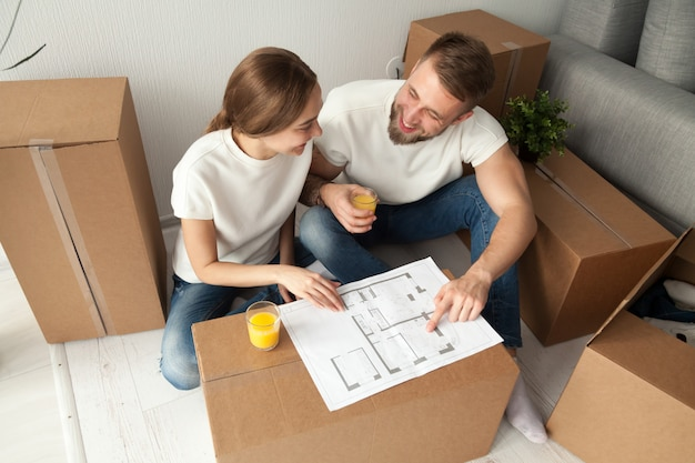 Pareja discutiendo el plan de la casa sentado en el piso con cajas en movimiento Foto gratis