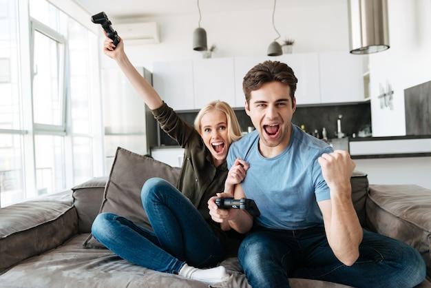 Pareja divertida jugando videojuegos y mirando la cámara Foto gratis