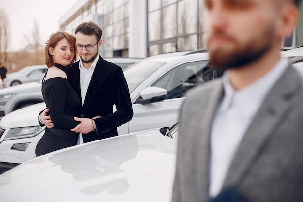Pareja elegante y elegante en un salón de autos. Foto gratis