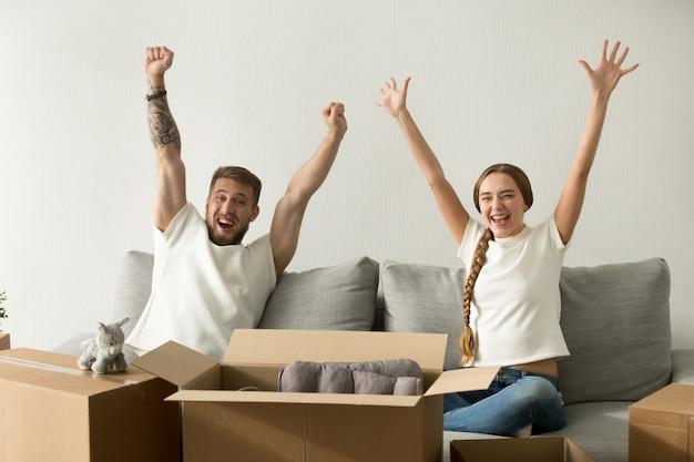 Pareja emocionada levantando manos felices de mudarse a casa nueva Foto gratis