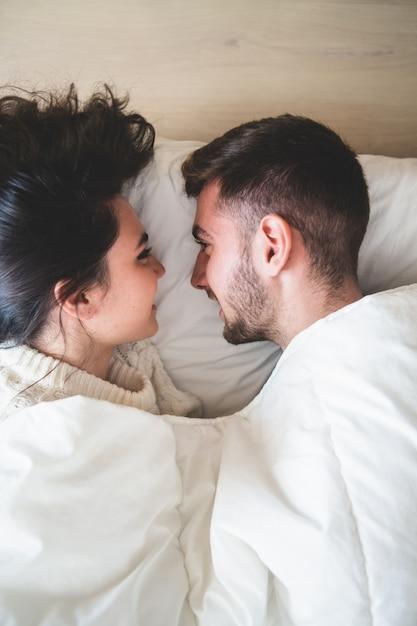 Pareja en la cama mirándose a los ojos y sonriendo | Descargar Fotos ...