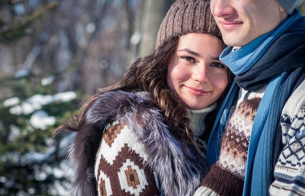 Pareja de enamorados abrazos en winter park Foto Premium
