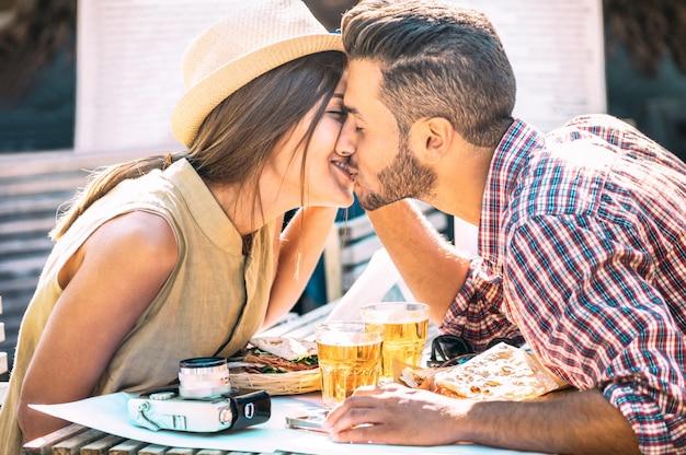 Pareja de enamorados besándose en el bar comiendo comida local en una excursión de viaje Foto Premium