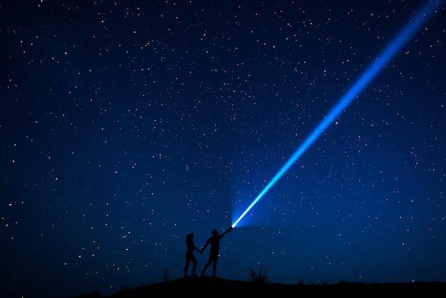 Pareja de enamorados camina bajo las estrellas. silueta de pareja de amantes que están disfrutando de su tiempo juntos en la noche bajo un cielo estrellado. cielo estrellado. caminata nocturna. hombre y mujer viajando. viaje de la boda Foto Premium