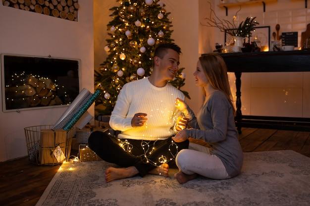 Pareja de enamorados en casa en el árbol de navidad en el fondo luz mágica Foto Premium