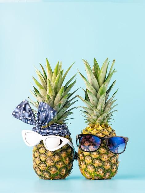 Pareja de enamorados de compras en un resort de vacaciones. piñas con gafas en forma de un chico y una chica sobre un fondo claro Foto Premium