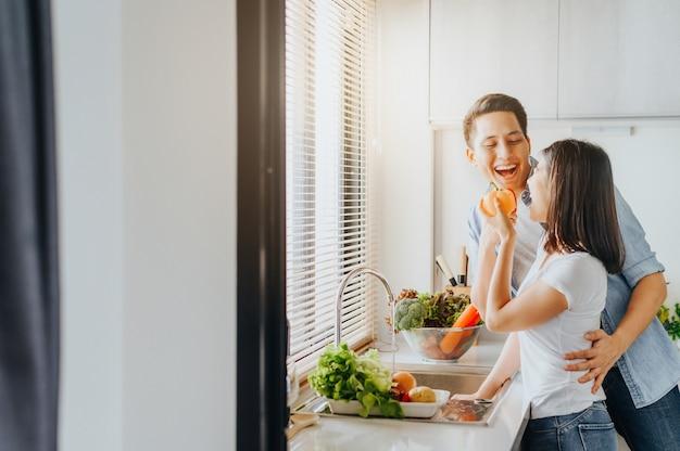 Pareja de enamorados sonriendo y diviértete mientras cocinas en la cocina Foto Premium