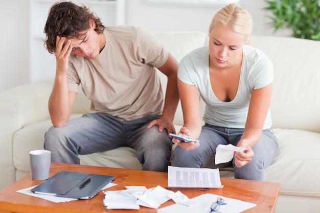 Pareja estresada calculando sus gastos | Foto Premium