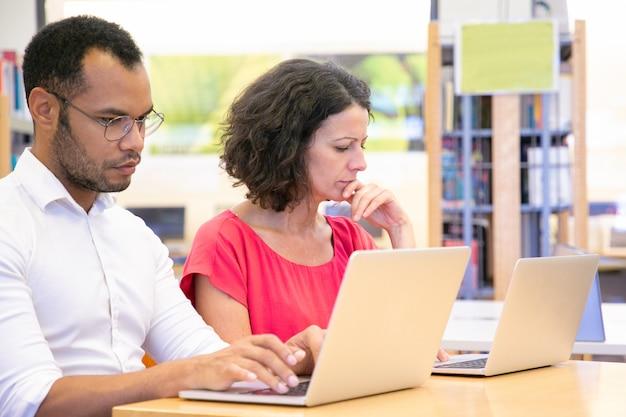 Pareja de estudiantes adultos serios trabajando en proyecto en biblioteca Foto gratis