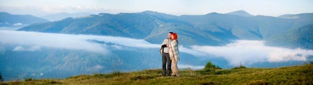 Pareja de excursionistas cubiertos con una manta de pie juntos en una colina Foto Premium