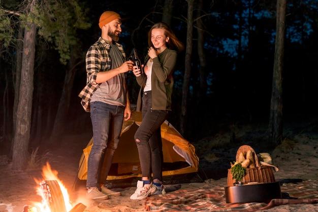 Pareja feliz acampando en la noche Foto gratis