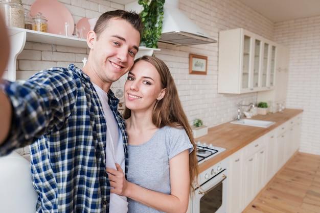 Pareja feliz en el amor haciendo selfie en cocina Foto gratis