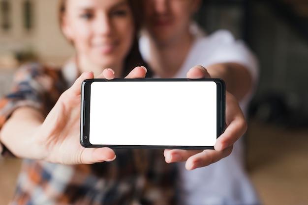 Pareja feliz en el amor que muestra la pantalla del teléfono inteligente Foto gratis