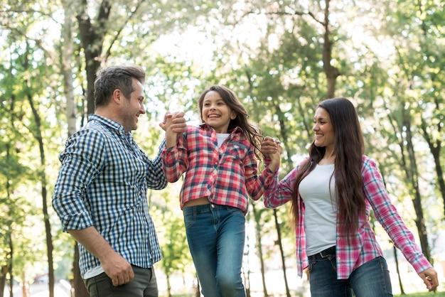 Pareja feliz balanceando a su hija entre ellos en el parque Foto gratis