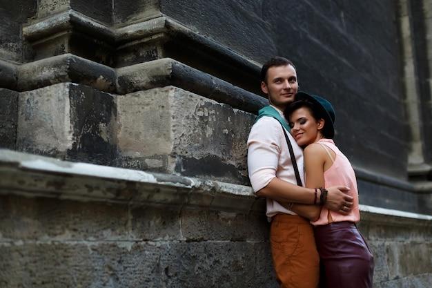 Pareja feliz en una calle de la ciudad. mujer joven con un sombrero y una falda de cuero y un hombre gentil abrazando en la calle. amor e historia de amor Foto Premium