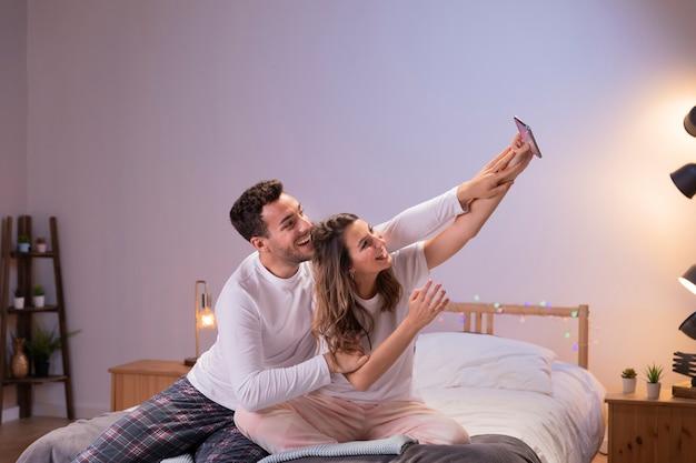 Pareja feliz en la cama tomando selfie Foto gratis