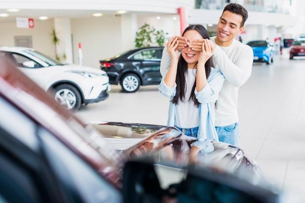 Pareja feliz en concesionario de coches Foto gratis