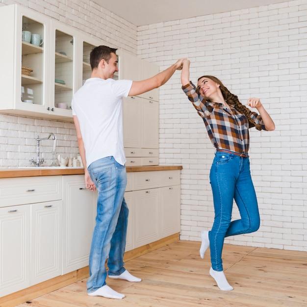Pareja feliz enamorada bailando en la cocina Foto gratis